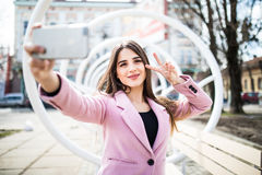 Закройте вверх по selfie-портрету милой девушки на улице на предпосылке города городской с знаком победы Стоковое Фото
