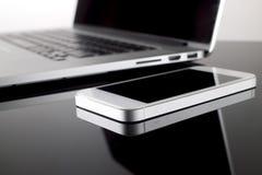 Закройте вверх по Smartphone на таблице с предпосылкой нерезкости компьтер-книжки techno Стоковые Изображения