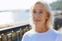 Закройте вверх приятной старшей женщины стоя на мосте Стоковое Изображение RF