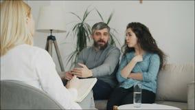 Закройте вверх профессиональных примечаний сочинительства психолога и слушая молодых пар которые споря и говоря один другого видеоматериал