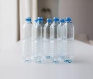Закройте вверх пустых используемых пластичных бутылок на таблице Стоковые Фото