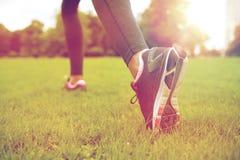 Закройте вверх работать ноги женщины на траве в парке Стоковое Изображение RF