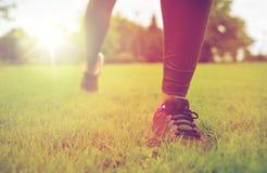 Закройте вверх работать ноги женщины на траве в парке Стоковое Изображение