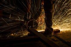 Закройте вверх работника металла используя угловую машину к отрезанному металлическому стержню стоковая фотография rf