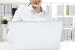 Закройте вверх работника офиса усмехаясь на ее компьтер-книжке Стоковые Фото