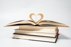 Закройте вверх раскрытой книги при сердце сформированное от 2 страниц, изолированных на белой предпосылке стоковое фото rf