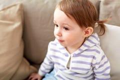 Закройте вверх ребёнка сидя на софе дома Стоковые Фотографии RF