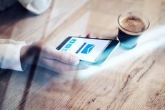 Закройте вверх родового smartphone дизайна при электронная почта посылая экран значков держа в женской руке Эспрессо чашки на таб Стоковое Изображение RF