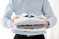 Закройте вверх рубашек бизнесмена сложенных удерживанием стоковые изображения rf