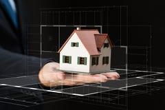 Закройте вверх руки бизнесмена держа модель дома Стоковое Изображение RF