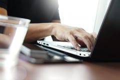 Закройте вверх руки бизнесмена работая на портативном компьютере Стоковые Фото