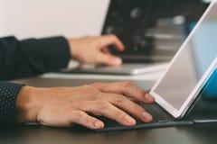 закройте вверх руки бизнесмена работая с компьтер-книжкой и цифровым doc Стоковые Изображения