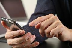 закройте вверх руки бизнесмена работая с мобильным телефоном и lapto Стоковая Фотография RF