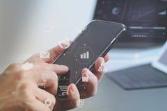 закройте вверх руки бизнесмена работая с мобильным телефоном и lapto Стоковое Изображение