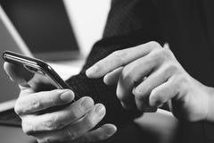 закройте вверх руки бизнесмена работая с мобильным телефоном и lapto Стоковые Фото