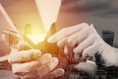 закройте вверх руки бизнесмена работая с мобильным телефоном и lapto Стоковая Фотография