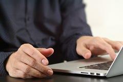 закройте вверх руки бизнесмена работая с портативным компьютером в mod Стоковые Фотографии RF