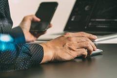 закройте вверх руки бизнесмена работая с умными телефоном и компьтер-книжкой Стоковое Изображение