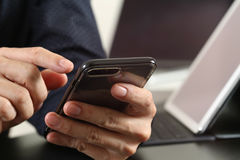 закройте вверх руки бизнесмена работая с умными телефоном и компьтер-книжкой Стоковые Фото