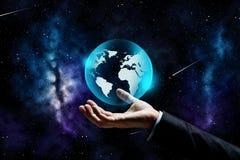 Закройте вверх руки бизнесмена с проекцией земли Стоковые Изображения