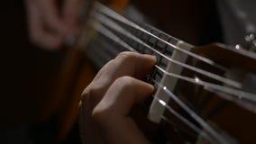 Закройте вверх руки гитариста играя акустическую гитару Закройте вверх по съемке человека с его пальцами на ладах гитары Стоковое Изображение
