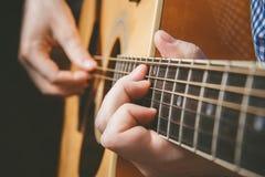 Закройте вверх руки гитариста играя гитару Стоковое Изображение RF