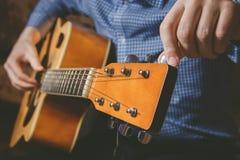 Закройте вверх руки гитариста играя гитару Стоковая Фотография
