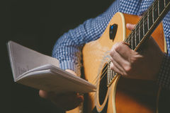 Закройте вверх руки гитариста играя гитару Стоковые Фотографии RF