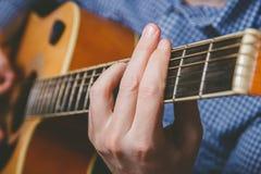Закройте вверх руки гитариста играя гитару Стоковое Фото