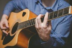 Закройте вверх руки гитариста играя гитару Стоковые Изображения