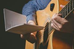 Закройте вверх руки гитариста играя гитару Стоковое Изображение