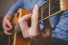 Закройте вверх руки гитариста играя гитару Стоковая Фотография RF