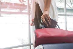 Закройте вверх руки женщины держа пасспорт и волоча чемодан багажа Стоковое фото RF