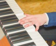 Закройте вверх руки женщины играя рояль Стоковые Фото