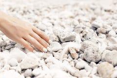 Закройте вверх руки женщины с маникюром на предпосылке Pebble Beach Стоковая Фотография