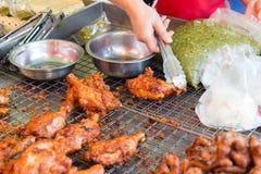 Закройте вверх руки кашевара при схваты жаря цыпленка Стоковое фото RF