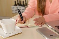 Закройте вверх руки коммерсантки работая и держа с одной рукой ручка и писать на повестке дня план-график деятельности Стоковое Фото