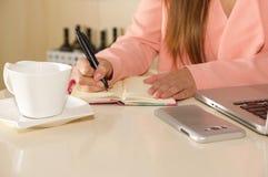 Закройте вверх руки коммерсантки работая и держа с одной рукой ручка и писать на повестке дня план-график деятельности Стоковая Фотография RF