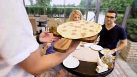 Закройте вверх руки мужского кельнера в белой рубашке принося вкусную горячую итальянскую пиццу для клиентов Родители с маленьким сток-видео