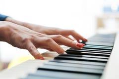 Закройте вверх руки пианистов играя рояль Отмело глубоко поля стоковые фото