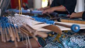 Закройте вверх руки сплетя с ручками, делающ традиционный саронг в Индонезии сток-видео