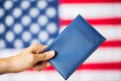 Закройте вверх руки с американским пасспортом стоковые изображения