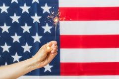 Закройте вверх руки с бенгальским огнем над американским флагом стоковые фото