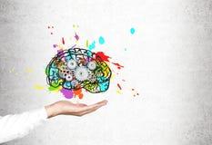 Закройте вверх руки человека с мозгом, шестернями, конкретными Стоковая Фотография RF