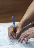 Закройте вверх руки человека с сочинительством и подписанием ручки стоковое изображение rf
