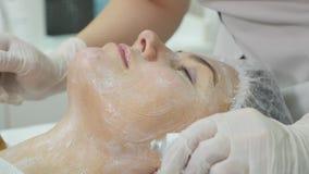Закройте вверх руки cosmetologist прикладывая cream маску на женской стороне Она держит щетку Красивая молодая женщина видеоматериал