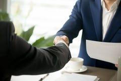 Закройте вверх рукопожатия дела, мужских рук тряся после подписания Стоковое фото RF