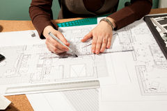 Закройте вверх рук архитектора работая на светокопиях Стоковые Изображения