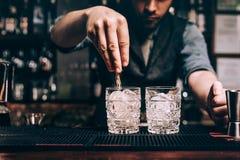 Закройте вверх рук бармена лить сахар в старомодном коктеиле свежие напитки на баре стоковое фото