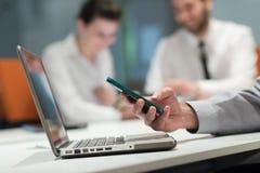 Закройте вверх рук бизнесмена используя умный телефон на встрече Стоковые Изображения RF